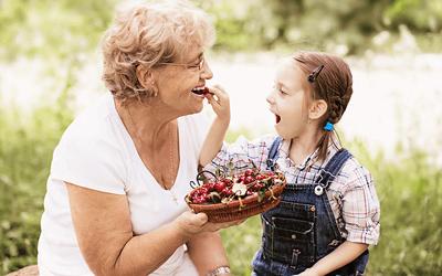 Enkelin füttert ihre Oma mit Kirschen